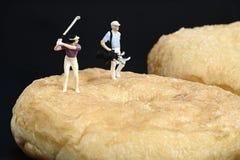 Miniaturleute, die Golf spielen Stockbild