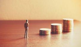 Miniaturleute, die mit Stapelmünze über Finanz zukünftig schauen Lizenzfreies Stockbild