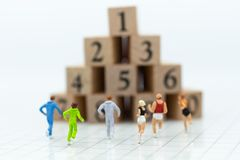 Miniaturleute, die zum Stapel des Zahlholzklotzes laufen Bildgebrauch für gesundes, Übungskonzept Lizenzfreie Stockbilder