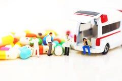 Miniaturleute: Doktor und geduldige Stellung mit Krankenwagen und Drogen lizenzfreie stockfotografie