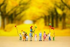 Miniaturleute: Familie, die Ballone mit Parkhintergrund hält Lizenzfreies Stockfoto