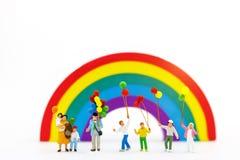 Miniaturleute: Familie und Kinder genießen mit bunten Ballonen auf Regenbogen, stockfotografie