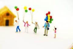 Miniaturleute: Familie und Kinder genießen mit bunten Ballonen und Haus lizenzfreie stockfotos