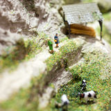 Miniaturleute: Frau zwei, die auf einem Gebirgsweg steht und nahe dem Weiden lassen von Kühen spricht Makrofoto, flacher DOF Stockbilder
