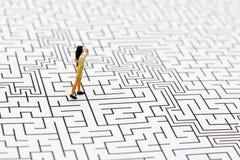 Miniaturleute: Geschäftsfrau, die auf Mitte des Labyrinths steht Conc stockbilder