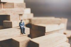 Miniaturleute: Geschäftsleute, die auf hölzernem Block sitzen Stockbilder