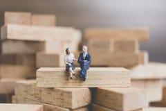 Miniaturleute: Geschäftsleute, die auf hölzernem Block sitzen Lizenzfreies Stockfoto