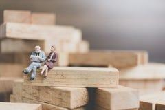 Miniaturleute: Geschäftsleute, die auf hölzernem Block sitzen Lizenzfreie Stockfotografie