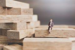 Miniaturleute: Geschäftsleute, die auf hölzernem Block sitzen Lizenzfreie Stockbilder