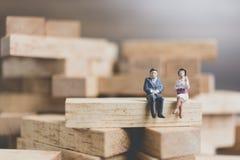 Miniaturleute: Geschäftsleute, die auf hölzernem Block sitzen Lizenzfreie Stockfotos