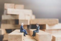 Miniaturleute: Geschäftsleute, die auf hölzernem Block sitzen Lizenzfreies Stockbild