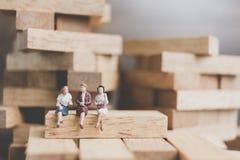 Miniaturleute: Geschäftsleute, die auf hölzernem Block sitzen Stockfoto