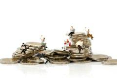 Miniaturleute: Geschäftsmänner, die auf Münzen sitzen und Nachrichten lesen lizenzfreie stockbilder