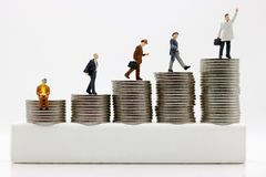 Miniaturleute: Geschäftsmänner, die zur Spitze des Münzgelds gehen Stockbild