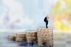 Miniaturleute: Geschäftsmänner, die zur Spitze des Münzgelds gehen Lizenzfreies Stockfoto