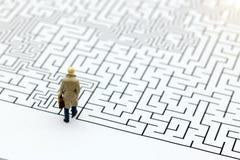 Miniaturleute: Geschäftsmann, der auf Anfang des Labyrinths steht Lizenzfreies Stockfoto