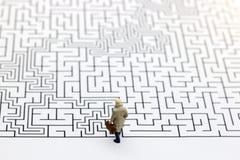 Miniaturleute: Geschäftsmann, der auf Anfang des Labyrinths steht Stockfotografie