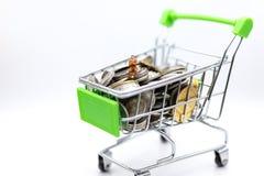 Miniaturleute: Geschäftsmann, der auf Einkaufswagen auf Stapel der Münze sitzt Bildgebrauch für Einzelhandelkonzept stockbilder