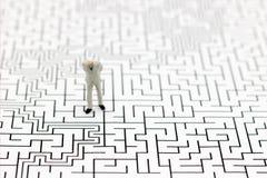 Miniaturleute: Geschäftsmann, der auf Mitte des Labyrinths steht Stockfotografie