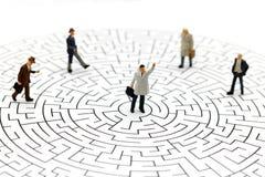 Miniaturleute: Geschäftsmann, der auf Mitte des Labyrinths steht Stockfoto