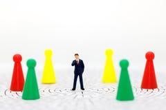 Miniaturleute: Geschäftsmann, der auf Mitte des Labyrinths steht Concep Lizenzfreie Stockbilder