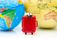 Miniaturleute: Geschäftsmann, der auf rotem Koffer, Weltkarte für Hintergrund sitzt Bildgebrauch für Reise, Geschäftskonzept Lizenzfreies Stockbild