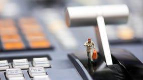 Miniaturleute: Geschäftsmann, der Uhr und Weg auf betrachtet Stockfotografie