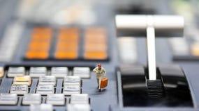Miniaturleute: Geschäftsmann, der Uhr und Weg auf betrachtet Stockfoto