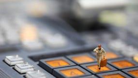 Miniaturleute: Geschäftsmann, der Uhr und Weg auf betrachtet Stockfotos