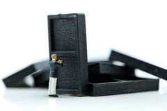 Miniaturleute: Geschäftsmann mit Stapel fallenden Dominos, b Stockfoto