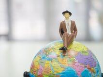 Miniaturleute, Geschäftsmann sitzen auf der Weltkarte und kopieren s Lizenzfreie Stockfotografie