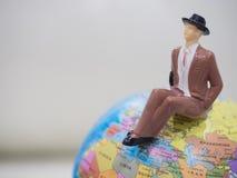 Miniaturleute, Geschäftsmann sitzen auf der Weltkarte und kopieren s Lizenzfreie Stockbilder