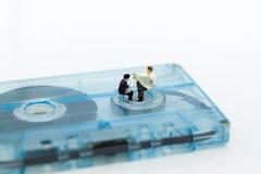 Miniaturleute: Geschäftsmann sitzen und Lesezeitung auf kompakter Kassette Bildgebrauch für Musik, Geschäftskonzept Stockfotos