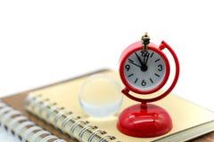 Miniaturleute: Geschäftsmann, sitzend auf roter Uhr mit dem Buch stockfotografie