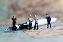 Miniaturleute: Geschäftsmannhändedruck auf der Weltkarte Lizenzfreie Stockfotos