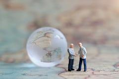 Miniaturleute: Geschäftsmannhändedruck auf der Weltkarte Stockfoto