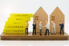 Miniaturleute: Geschäftsmannhändedruck zu Geschäftserfolg mit Holzhäusern Verpflichtung, Vereinbarung, Investition und Partnersch stockfoto