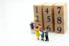 Miniaturleute: Geschäftsmannlesebuch mit Holzklotz Bildgebrauch für Hintergrundbildung oder Geschäftskonzept Stockbilder