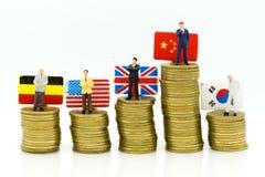 Miniaturleute: Geschäftsmannstand auf Stapel prägt mit Landesflagge, zeigen die Gewinne des Marketings in jedem Land Stockfotografie