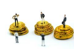 Miniaturleute: Geschäftsmannstand mit Goldmünzen Lizenzfreie Stockfotografie