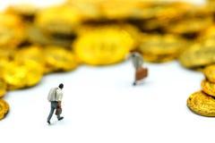 Miniaturleute: Geschäftsmannstand mit Goldmünzen Stockfoto