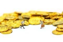 Miniaturleute: Geschäftsmannstand mit Goldmünzen Lizenzfreies Stockfoto