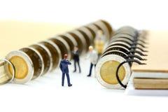Miniaturleute: Geschäftsmannstand mit Münzen des Buches, educatio Lizenzfreie Stockfotos