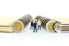 Miniaturleute: Geschäftsmannstand mit Münzen des Buches, educatio Stockfotografie