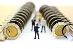 Miniaturleute: Geschäftsmannstand mit Münzen des Buches, educatio Stockfoto