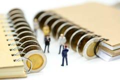 Miniaturleute: Geschäftsmannstand mit Münzen des Buches, educatio Lizenzfreie Stockfotografie