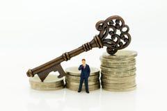 Miniaturleute: Geschäftsmannstand mit Schlüsseln Bildgebrauch für Schlüsselfigur, der Schlüssel zum Erfolg, Geschäftskonzept Lizenzfreie Stockbilder