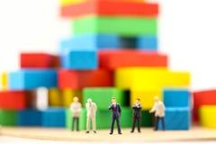 Miniaturleute: Geschäftsmannteam, das mit buntem woode steht Stockbilder