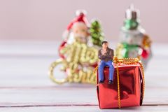 Miniaturleute: Geschäftsmannzahlen, die auf der Geschenkbox sitzen Lizenzfreies Stockfoto