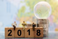 Miniaturleute: Geschäftsteamlesung auf hölzernem Block Lizenzfreie Stockfotos